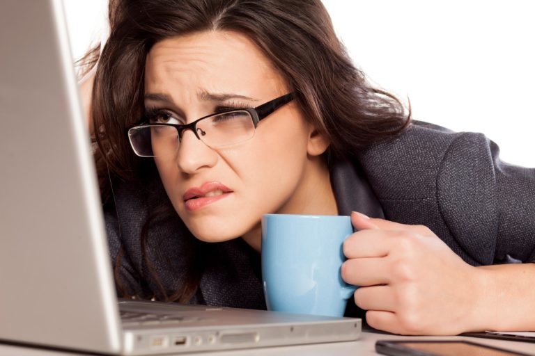 A woman with glasses holding a cup looks closely on a laptop with a frowning face